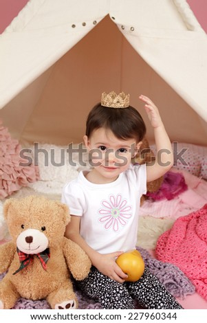 Toddler child, kid, engaged in pretend play with princess crown and teepee tent - stock photo