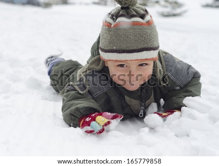 Toddler child playing in a snow in winter.  - stock photo