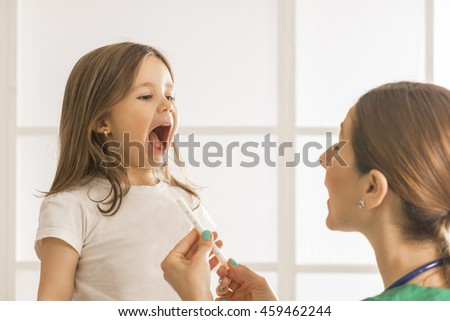 Toddler child take an oral medical suspension with syringe. Young female doctor giving little girl medicine
