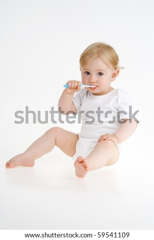 Toddler clears teeth on white background.