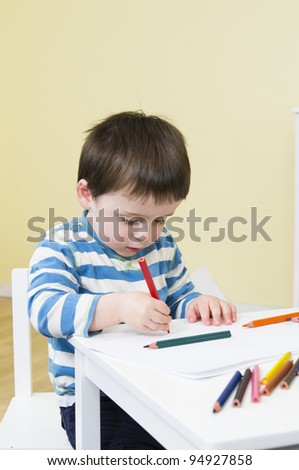 Toddler concentrates while drawing