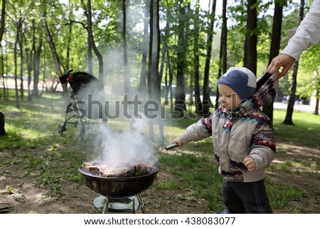 Toddler cooking sausages on a grill at picnic