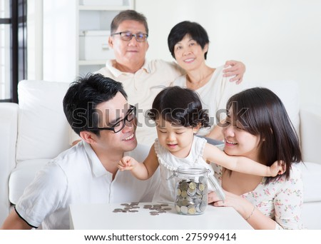 Toddler counting coins. Asian family money savings concept. Multi generations living lifestyle at home. - stock photo