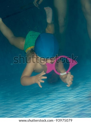 Toddler Diving to catch a toy underwater exercise in the pool - stock photo