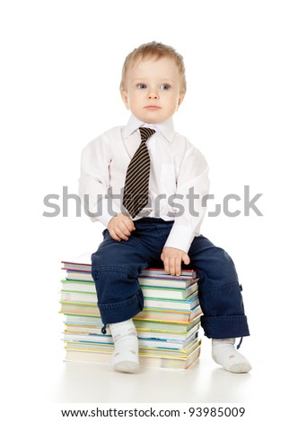 toddler dressed in suit and sitting on the heap of books - stock photo