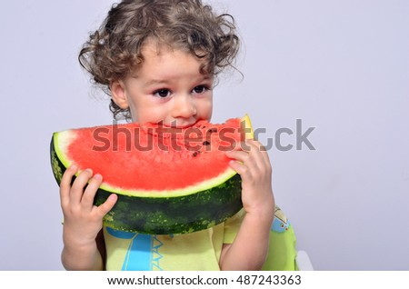 Toddler eating a slice of a sweet delicious watermelon. Hungry kid biting from a piece of melon and getting messy