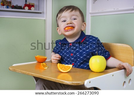 Toddler eating fruit and being naughty - stock photo
