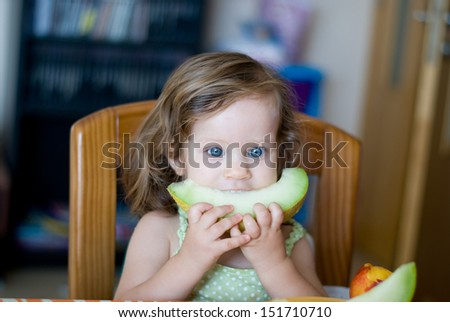 Toddler Eats  melon  on the table - stock photo