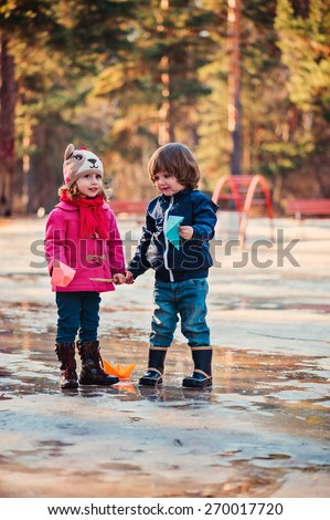 toddler friend playing in puddle in early spring forest - stock photo