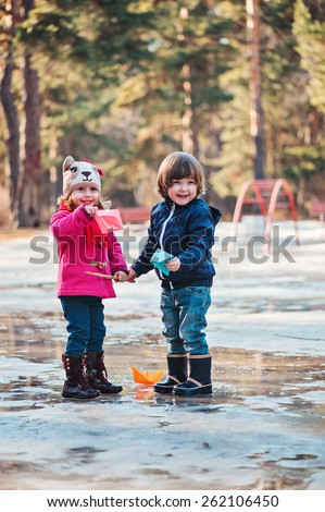 toddler girl and boy are happy on the early spring walk with paper boats in hands