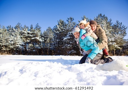 Toddler girl and her parents in a snowy park