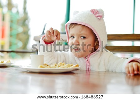 toddler girl eating in outdoor cafe