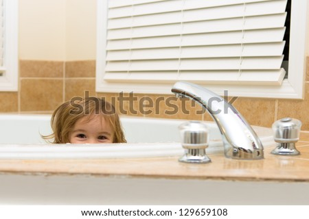 Toddler girl giving happy hiding look from the bathtub, perhaps she does not want to take a bath - stock photo