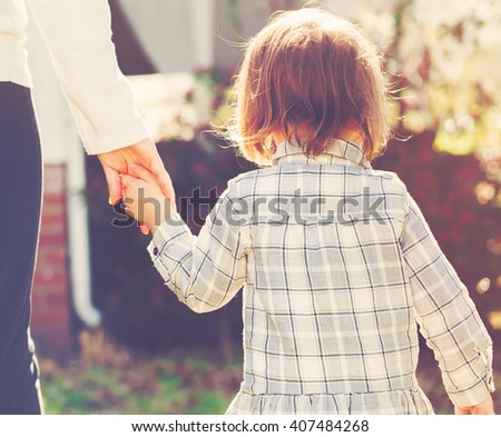 Toddler girl holding hands with her mother outside - stock photo
