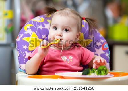 toddler girl in a highchair for feeding with fork and plate at home - stock photo