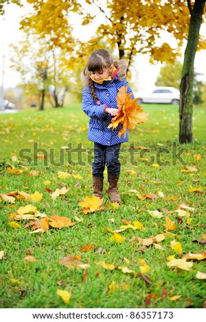 Toddler girl in blue coat picking up leaves on a meadow - stock photo