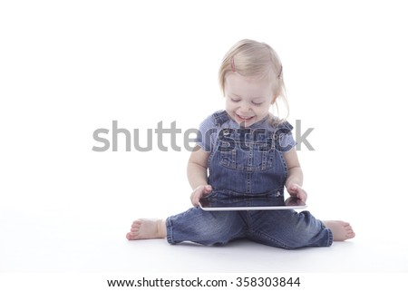 toddler girl in overalls, reading a tablet, isolated on white