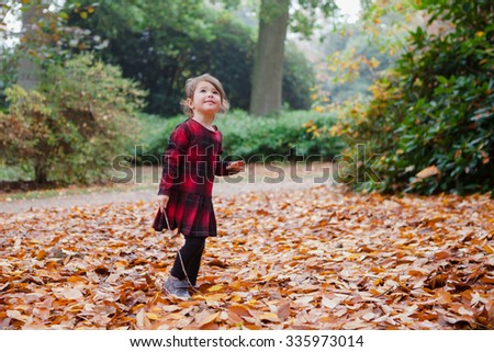 Toddler girl in red and black tartan dress playing with falling leaves and sticks, selective focus