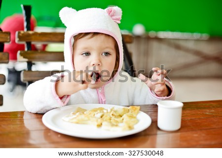 toddler girl is eating in outdoor cafe - stock photo