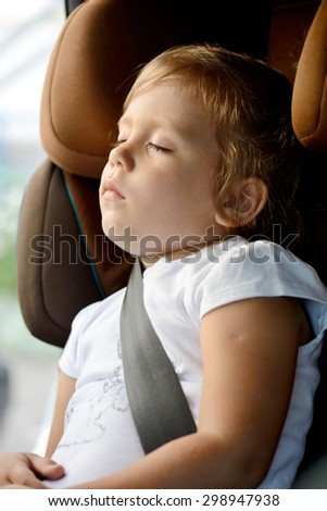 toddler girl is sleeping in  the car seat - stock photo