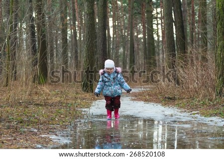 Toddler girl is walking on big early spring icy puddle - stock photo