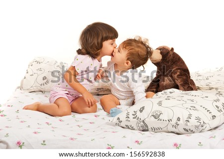 Toddler girl kissing a baby boy and sitting together in bed with teddy bear - stock photo