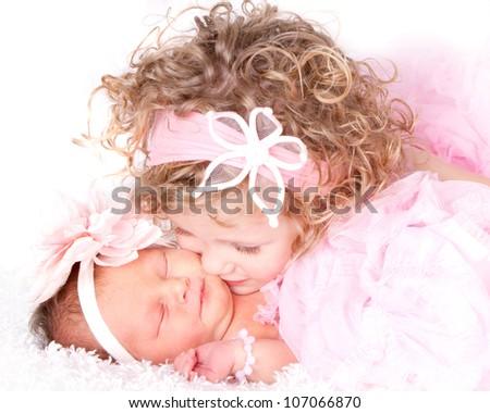 Toddler girl kissing her sleeping baby/infant sister - stock photo
