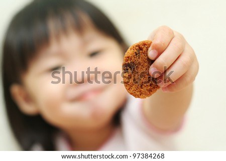 Toddler girl offering you a chocolate chip cookie - stock photo