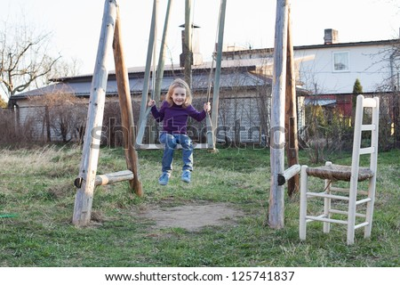 Toddler girl on a swing in the village