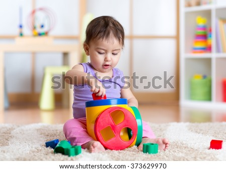 toddler girl playing indoors with sorter toy sitting on soft carpet - stock photo