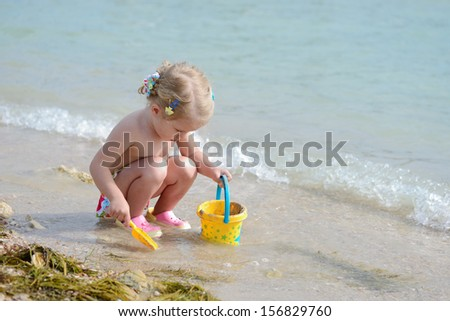 toddler girl playing on the beach with sand - stock photo