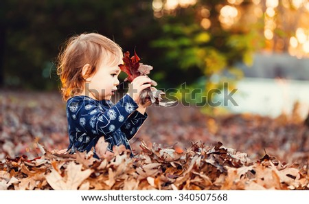 Toddler girl playing outside in a pile of autumn leaves at sunset - stock photo