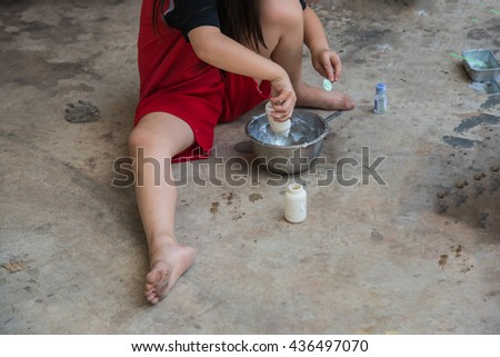 Toddler girl playing toy kitchen on ground - stock photo