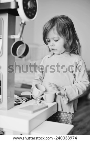 toddler girl playing with kitchen at home - stock photo