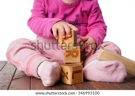 Toddler Girl playing with wooden blocks, cubes. Isolated on White - stock photo