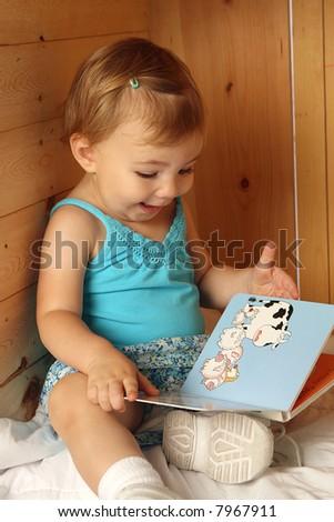 toddler girl reading a board book - stock photo