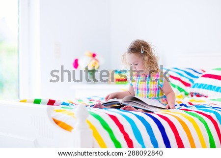 Toddler girl reading a book in bed. Children read books. Kids learning. Preschool kid doing homework in bedroom. Colorful textile bedding for child and baby room. Preschoolers learn and study at home - stock photo