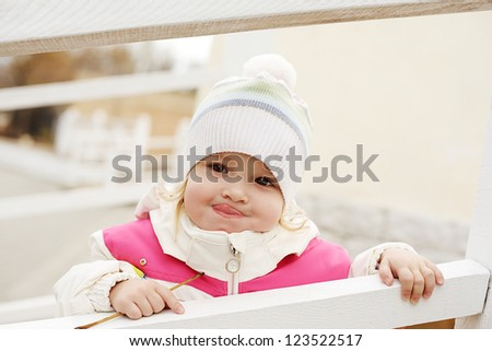 toddler girl showing tongue near fence