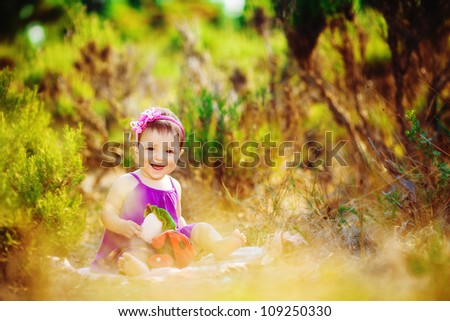 Toddler girl  sitting in summer green park outdoor - stock photo