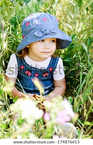 toddler girl sitting in the green grass