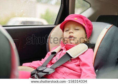 toddler girl sleeping in car seat - stock photo