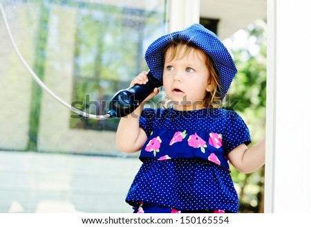 toddler girl speaking on the paystation - stock photo