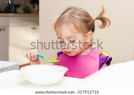 Toddler girl trying to eat soup by herself. Baby sitting in dining room, wearing a bib. Selective focus on child eyes. - stock photo