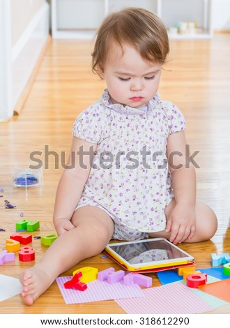 Toddler girl using a tablet computer amongst her toys - stock photo