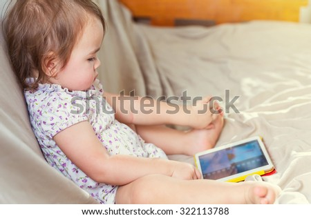 Toddler girl watching cartoons on her tablet computer - stock photo