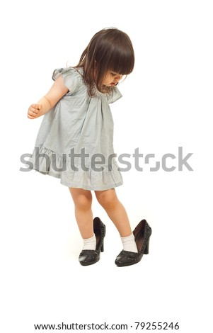 Toddler girl wearing big shoes and looking down with attentive face