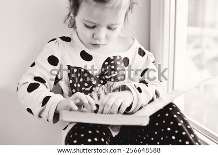 toddler girl with book near the window - stock photo