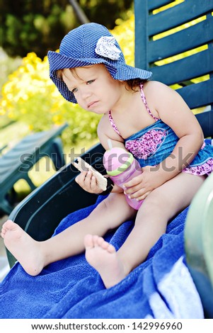 toddler girl with crisp and water sitting on sun lounger - stock photo