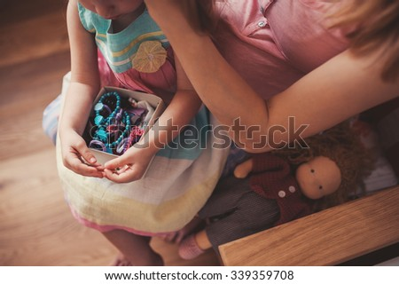 toddler girl with hair accessories with her mother at home - stock photo
