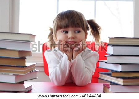 Toddler girl with pile of books on the table - stock photo